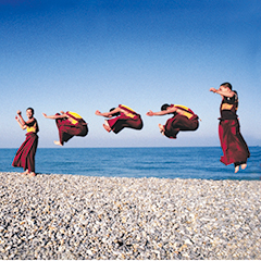 585. On a bright winter morning, Tibetan and Bhutanese monks jump for joy at the sight of the ocean. They will throw themselves up in the air again this evening, on the stage of a theatre in Brittany, France, defying gravity. This image is not a multiple exposure, but a single shot of seven monks jumping. 1997 Les moines volants du Toit du Monde devant l'océan Atlantique ; moines du monastère de Shéchèn au cours d'une tournée européenne de danses sacrées. 1997